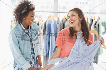 Happy women shopping in clothes store