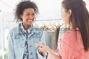Customer receiving credit card from saleswoman