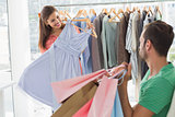 Man with shopping bags while woman selecting a dress