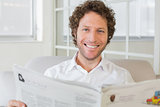 Smiling man reading newspaper at home