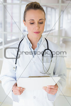 Beautiful female doctor with clipboard in hospital