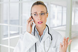 Beautiful female doctor using mobile phone