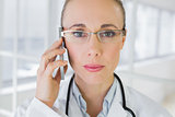 Closeup of a beautiful female doctor using mobile phone