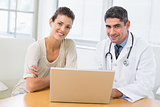 Doctor and patient using laptop in medical office