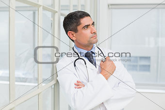 Thoughtful male doctor looking away in hospital