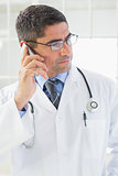 Serious male doctor using mobile phone