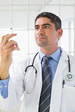 Serious male doctor holding an injection