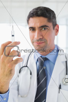 Portrait of male doctor holding an injection