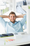 Handsome designer relaxing at his desk smiling at camera