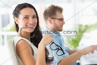 Beautiful designer smiling at camera at desk