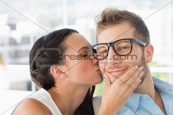 Attractive young designer getting a kiss from a co worker