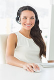 Smiling call centre agent sitting at her desk