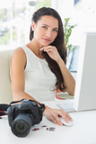 Focused photographer sitting at her desk using computer looking at camera