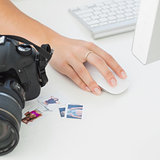Digital camera on photographers desk with womans hand on mouse