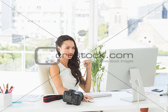 Beautiful focused photographer working at her desk