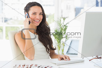 Beautiful editor talking on phone at her desk smiling at camera