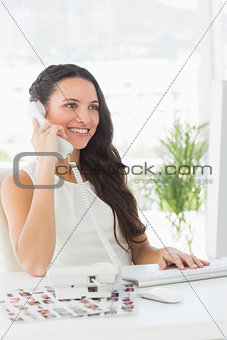 Beautiful editor on telephone at her desk