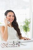 Beautiful editor on telephone at her desk smiling at camera