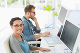 Team of young designers working at desk with woman smiling at camera