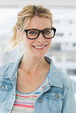 Pretty blonde designer wearing glasses smiling at camera