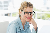 Blonde designer wearing glasses smiling at camera