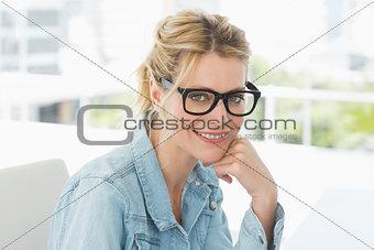 Blonde designer wearing glasses smiling at camera