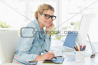 Blonde pretty designer looking at the camera using digitizer