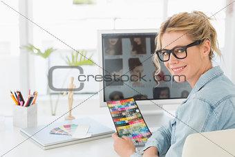 Blonde designer holding colour chart at her desk smiling at camera