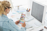 Blonde designer holding colour swatch at her desk