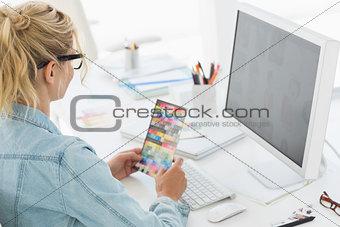 Blonde designer holding colour swatch at her desk