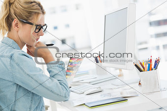Blonde focused designer working at her desk