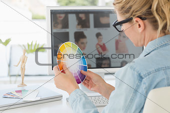 Blonde focused designer working at her desk holding a colour wheel