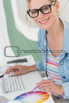 Blonde designer using a colour wheel smiling at camera