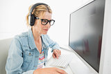 Blonde designer wearing headphones working at computer