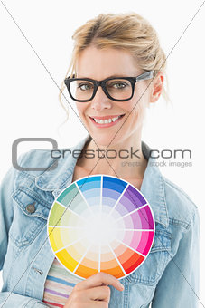 Blonde designer holding colour wheel smiling at camera