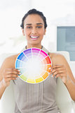 Happy designer at her desk showing colour wheel to camera
