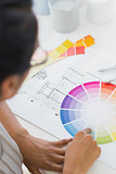 Interior designer looking at colour wheel at her desk