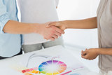 Interior designer shaking hands with customer