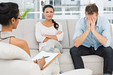Unhappy couple sitting on sofa at therapy session