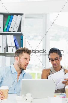 Focused partners working together on laptop at desk