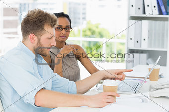 Casual business partners working together on laptop at desk