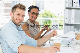 Business partners working together at desk smiling at camera