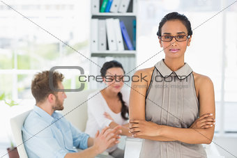 Attractive woman smiling at camera while colleagues chat at desk