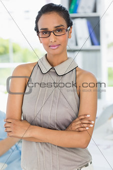Attractive woman smiling at camera with arms crossed