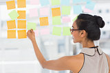 Smiling designer looking at sticky notes on window