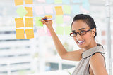 Smiling designer writing on sticky notes on window looking at camera
