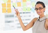 Designer pointing to sticky notes on window smiling at camera
