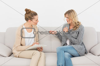 Blonde woman talking to her therapist on the couch