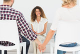 Happy therapist smiling at reconciled couple holding hands