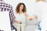 Concerned therapist handing a tissue to woman at couples therapy